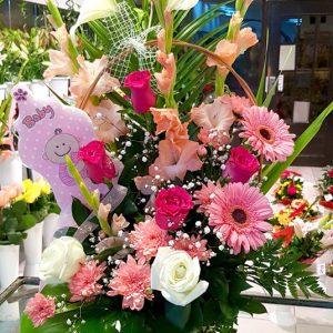 Aranžmani za rođenja – 001 – Bogata šarena korpa sa belim kraljevskim ljiljanima, rozim gerberima i rozim i belim ružama upotpunice poklon za svaku vašu proslavu.